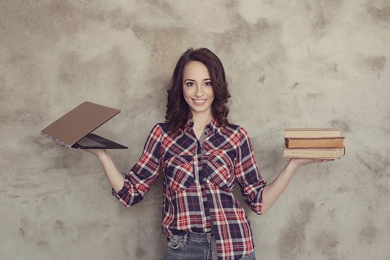 Cute woman balancing laptop and books